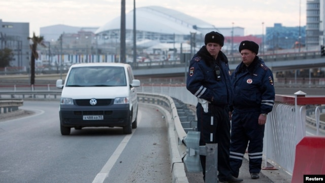 Russian traffic police stand guard on a road near venues at the Olympic Park near Sochi, January 7, 2014.