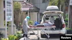 Petugas medis membawa pasien yang diduga terkena virus corona di rumah sakit Adam Malik Haji di Medan, Sumatera Utara, 18 Maret 2020. (Foto: Antara Foto / Septianda Perdana via REUTERS)