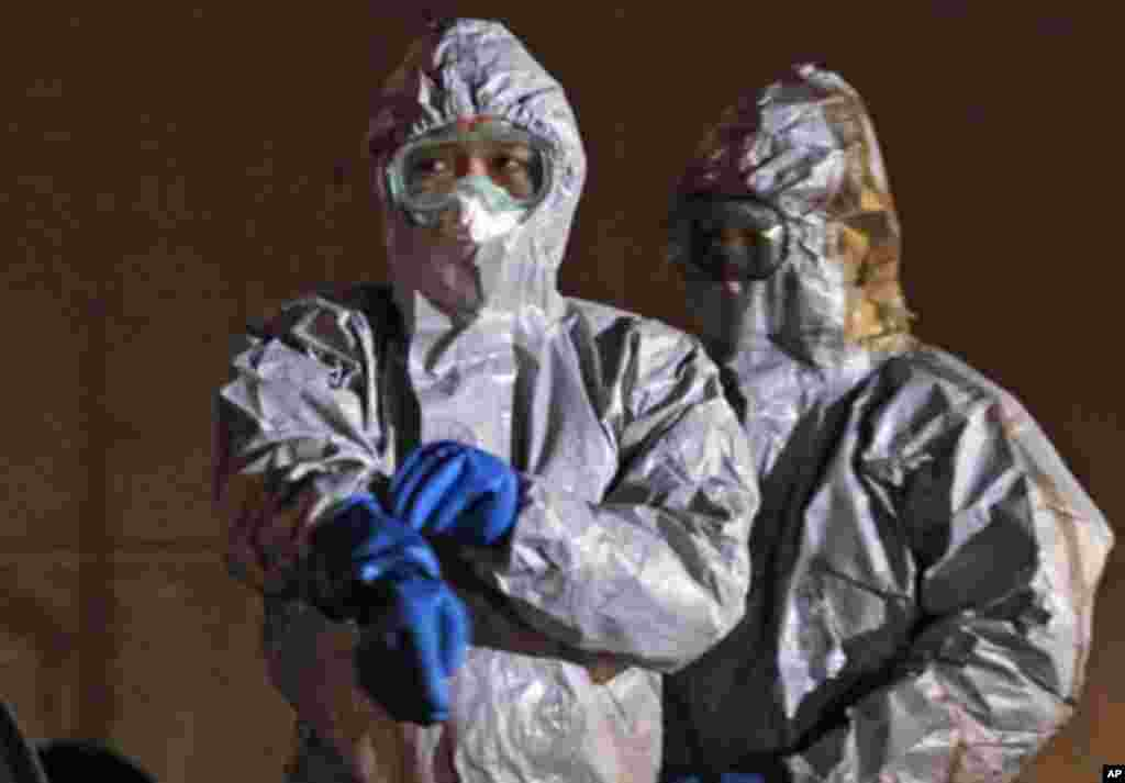 Officials in protective gear near the Fukushima Daiichi nuclear plant, in Koriyama, March 13, 2011