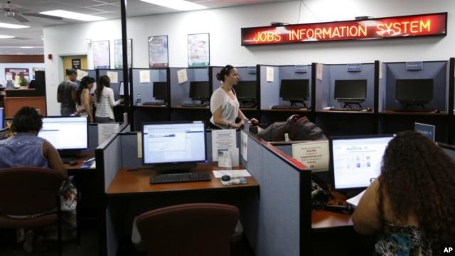 Người dân sử dụng máy tính để tìm kiếm việc tại công ty phát triển nhân lực.