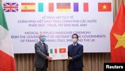 越南副外長蘇英勇(右)在一個贈送儀式上向意大利駐越南大使安東尼奧亞歷山德羅贈送防疫口罩。(2020年4月7日)