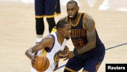 Tiền đạo Keven Durant của Warriors (áo số 35) đi bóng qua LeBron James (áo số 23) của Cavaliers trong trận chung kết hôm 1/6/ 2017 trên sân Oracle Arena ở Oakland, bang California.