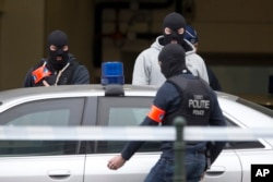 FILE - Police officers get into a vehicle outside a court building where Salah Abdeslam, the top suspect in the deadly, IS-claimed Paris attacks of the previous year, was expected to appear before a judge in Brussels, Belgium, March 24, 2016.