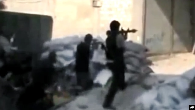 This image made from amateur video released by the Ugarit News, July 15, 2012, purports to show Free Syrian Army soldiers clashing with government forces in Damascus. (AP cannot independently verify the content, date, location or authenticity of this mate