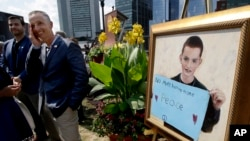 Bill Richard, second from left, father of Boston Marathon bombing victim Martin Richard, stands next to a painting of Martin, right, at the conclusion of groundbreaking ceremonies for a park named after his late son, Aug. 16, 2017, in Boston. Martin Richard, 8, was the youngest of three people killed when two bombs exploded near the Boston Marathon finish line on April 15, 2013.
