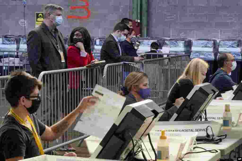 Election observers stand behind a barrier and watch as election office workers process ballots as counting continues from the general election at the Allegheny County elections returns warehouse in Pittsburgh, Friday, Nov. 6, 2020. (AP Photo/Gene J. Puska