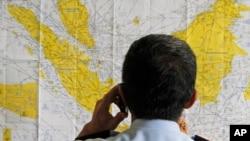 មន្រ្តីព្រលានយន្តហោះពិនិត្យមើលផែនទីប្រទេសឥណ្ឌូនេស៊ី។ យន្តហោះដឹកអ្នកដំណើរជើងហោះហើរ QZ8501 របស់ក្រុមហ៊ុន AirAsia ដែលហោះពីប្រទេសឥណ្ឌូនេស៊ី ទៅសិង្ហបុរី បានបាត់ជាមួយមនុស្ស១៦២នាក់នៅក្នុងនោះ។