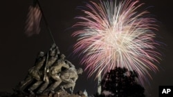 The United States Marine Corps War Memorial, better known as the Iwo Jima Memorial, in Arlington, Virginia, on July 4, 2011, as Independence Day fireworks burst over Washington. The Washington Monument and the Capitol are in the distance.