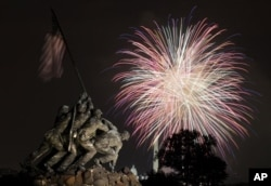 The United States Marine Corps War Memorial, better known as the Iwo Jima Memorial, in Arlington, Virginia, on July 4, 2011, as fireworks burst over Washington. The Washington Monument and the Capitol are in the distance.