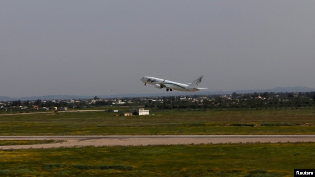 A plane is seen taking off as flights resume at the airport in Tripoli, Libya, March 21, 2014.