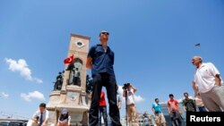 A man stands during a silent protest in Taksim Square in Istanbul June 18, 2013.
