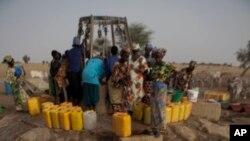 Djiba Ba charge 15 jerrycans d'eau sur une charrette tirée par un âne pour la ramener dans sa famille et ses animaux, dans le village de Mbelone dans la région de Matam au nord-est du Sénégal, le 1er mai 2012