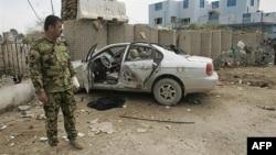 Polisi Irak berdiri di dekat sebuah mobil yang rusak dalam serangan bom bunuh diri di Baquba (foto: dok). Baquba diguncang serangan bunuh diri yang menewaskan 20 orang (6/4).