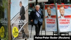 """FILE - A man passes by presidential election campaign posters of Alexander Van der Bellen (L), supported by the Greens, reading """"A president who unites"""" and Norbert Hofer of the Freedom Party (FPOe), reading """"The voice of reason"""" in Vienna, Austria, May 19, 2016."""