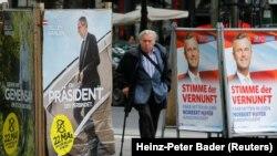 Seorang pria berjalan melewati poster kampanye pilpres Alexander Van der Bellen, kandidat dari Partai Hijau (kiri), dan Norbert Hofer, capres dari Partai Kebebasan (FPOe), di WIna, Austria, 19 Mei 2016 (Foto: dok).