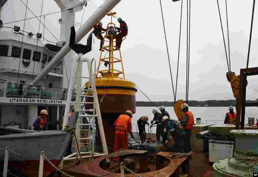 Members of a navigation ship KN Jadayat prepare a beacon buoy to begin the search operations for the wreckage of AirAsia Flight 8501 at Kumai Port in Pangkalan Bun, Indonesia, Jan. 5, 2015.