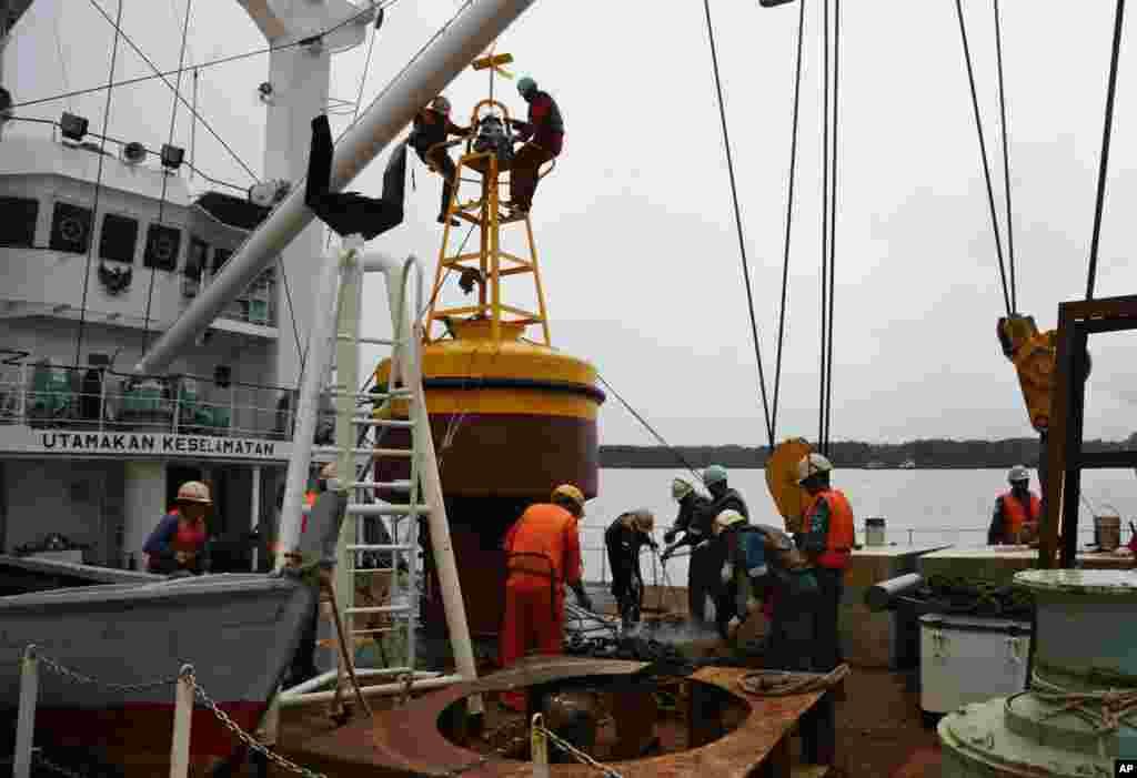 Para anggota kapal navigasi KN Jadayat mempersiapkan pelampung suar untuk memulai operasi pencarian bangkai pesawat AirAsia 8501 di Pelabuhan Kumai, Pangkalan Bun (5/1). (AP/Achmad Ibrahim)