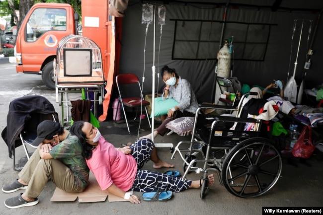 Seorang pasien COVID-19 beristirahat di luar tenda darurat yang didirikan di luar rumah sakit di tengah lonjakan kasus COVID-19 di Bekasi, 25 Juni 2021. (Foto: Willy Kurniawan/Reuters)