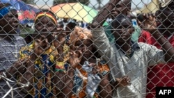 FILE - People stand behind a gate at Mpoko Airport in Bangui, Central African Republic, as food is being unloaded from a cargo aircraft.