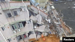 An aerial view shows rescuers looking for survivors at a damaged building after a landslide hit an industrial park in Shenzhen, Guangdong province, China, Dec. 21, 2015.