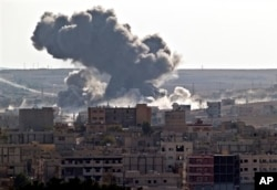 FILE - Smoke rises over the Syrian city of Kobani, following a US led coalition airstrike, seen from outside Suruc, on the Turkey-Syria border Monday, Nov. 10, 2014. Kobani, also known as Ayn Arab, and its surrounding areas, has been under assault by extremists