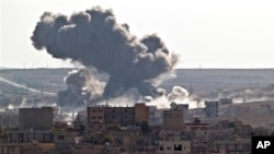 Smoke rises over the Syrian city of Kobani, following a US led coalition airstrike, seen from outside Suruc, on the Turkey-Syria border, Nov. 10, 2014. Kobani, also known as Ayn Arab, and its surrounding areas, has been under assault by extremists of the Islamic State group since mid-September and is being defended by Kurdish fighters. (AP Photo/Vadim Ghirda)
