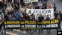 """Civil police demand better labor conditions as they carry a banner that reads in Portuguese """"The priority of the police is the people, the priority of the government is the Olympics"""" in Rio de Janeiro, Brazil, June 27, 2016."""