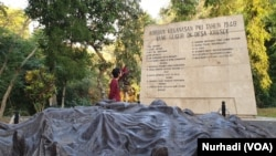 Seorang wisatawan membaca nama-nama korban kekejama n PKI di Monumen Kresek, Madiun. (Foto:VOA/ Nurhadi)