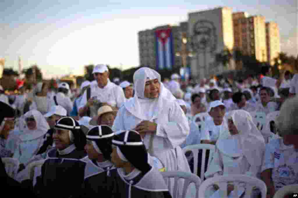 Nuns wait as worshippers gather in Revolution Square for the arrival of the Pope Benedict XVI to celebrate a Mass in Havana, Cuba, Wednesday, March 28, 2012. Pope Benedict XVI wraps up his visit to Cuba on Wednesday with an open-air Mass in the shrine of