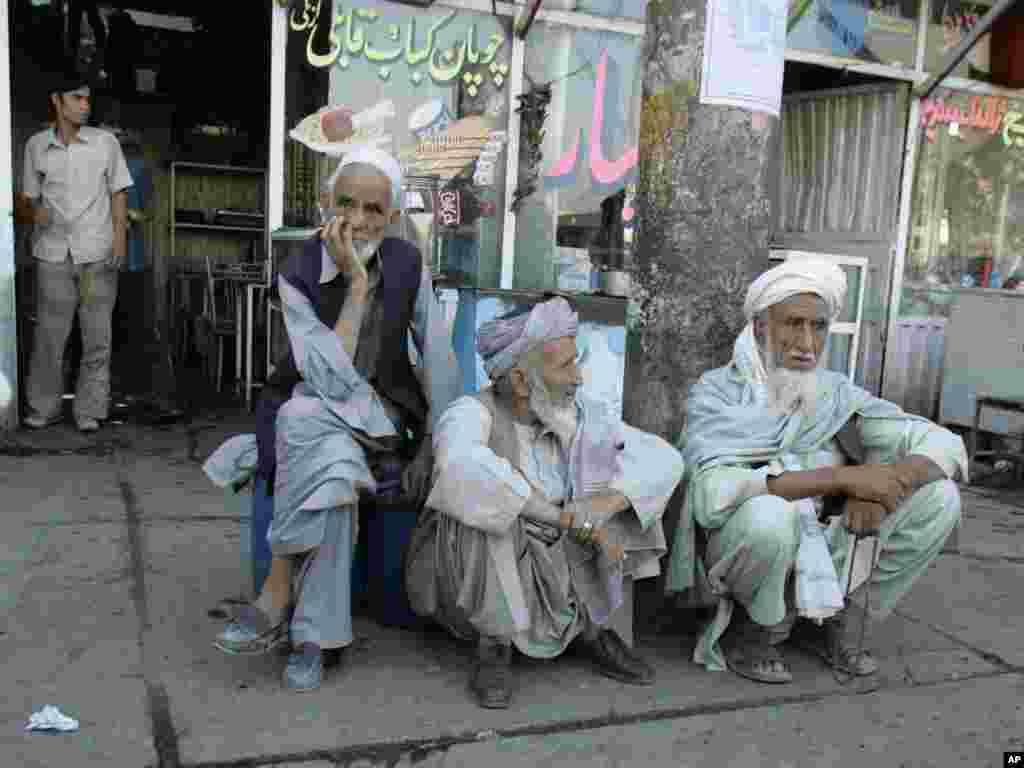 پیرمردان بازنشستۀ نظامی در نزدیکی دفتر تقاعد منتظر دریافت حقوق شان اند.