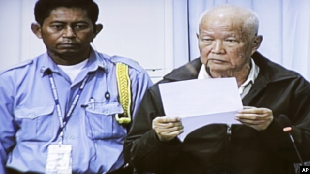 Khieu Samphan, right, former head of state, is seen in the video screen set up in the press center of the U.N.-backed war crimes tribunal on the outskirts of Phnom Penh, Cambodia, Thursday, June 30, 2011. The tribunal on Thursday held its fourth day trial