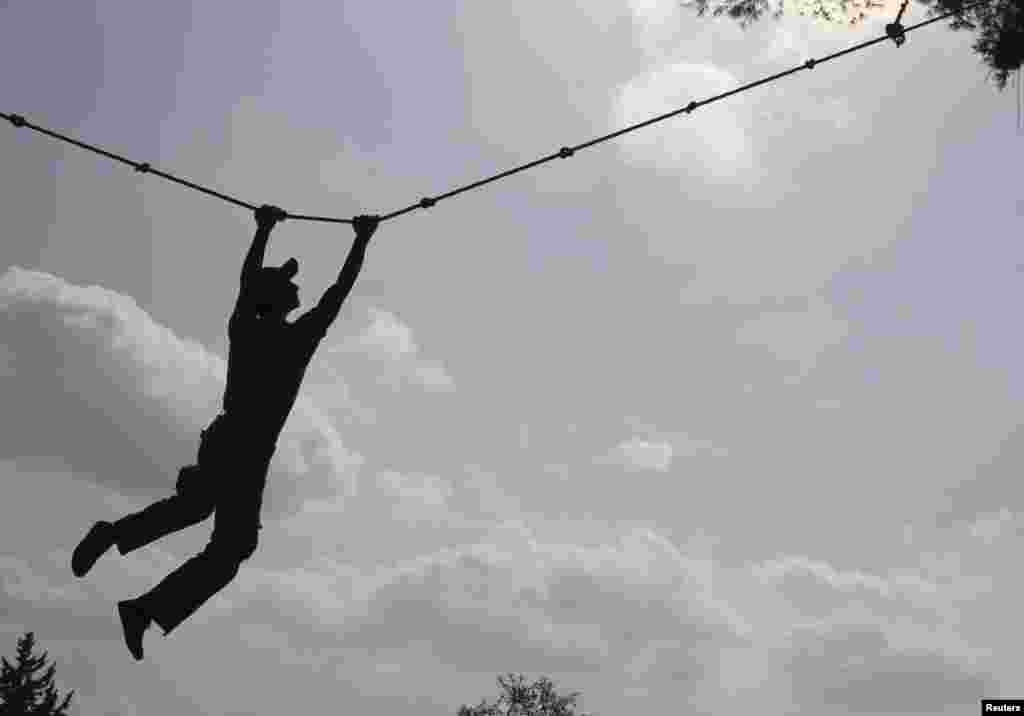 A Free Syrian Army fighter exercises on a rope during a training session at an FSA camp in the countryside of Idlib, October 23