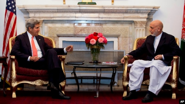 U.S. Secretary of State John Kerry, left, meets with Afghan President Hamid Karzai at the Presidential Palace during an unannounced stop in Kabul, Afghanistan, Oct. 11, 2013.