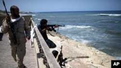 Rebel fighters shoot at what is allegedly Moammar Gadhafi's beach house in Tripoli, August 29, 2011