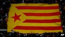 Demonstranti drže zastavu Katalonije tokom protesta u Barseloni (3. oktobar 2017)