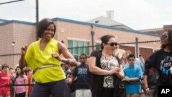 """美國第一夫人米歇爾•奧巴馬去年五月五日訪問華盛頓的一所學校﹐觀看學生做""""讓我們動起來""""的運動"""
