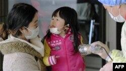 Мать и дочь проходят проверку на радиацию после эвакуации в Фукусиме. Япония, 18 марта 2011г.