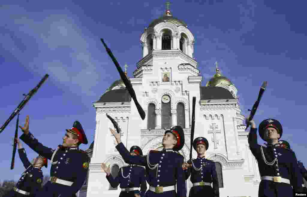 Cossack cadets toss their rifles as they practice for an upcoming performance to mark the 130th anniversary of the founding of the Novocherkassk Cossack cadet corps, outside a cathedral in the southern Russian city of Novocherkassk.
