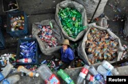 FILE - A laborer looks up as she sorts plastic bottles at a garbage recycling center in Hefei, Anhui province, China, May 20, 2014.