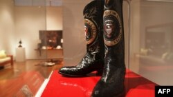 FILE - A pair of Ronald Reagan's cowboy boots sit in a case at Christie's prior to an auction in New York, Sept, 16, 2016. The boots sold Friday for $199,500.