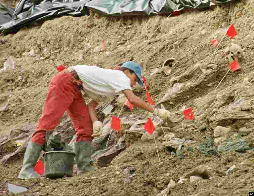 An international war crimes tribunal investigator carefully brushes away soil and debris as she works to unearth a jumble of bodies at a mass grave site near the village of Cerska, some 12 miles northeast of Srebrenica. (File 2006)