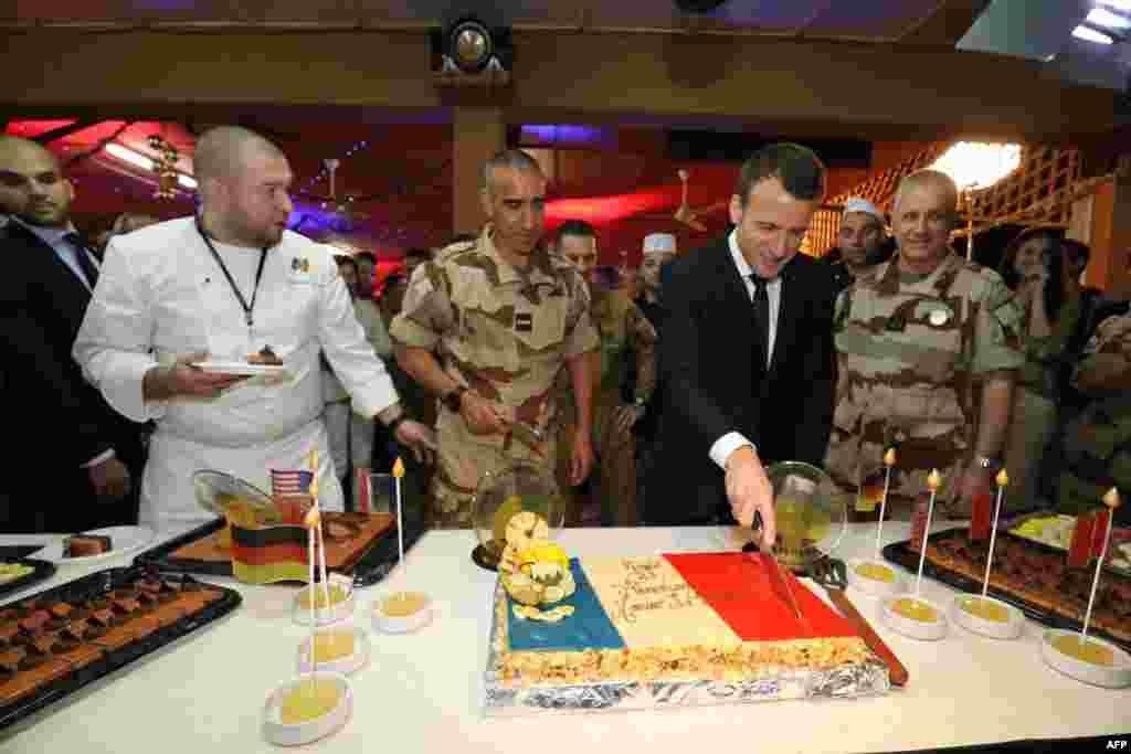 Le président français Emmanuel Macron va couper un gâteau couvert des couleurs du drapeau français alors qu'il assiste à un dîner de Noël avec 700 soldats français de la force anti-djihadiste française Barkhane, le 22 décembre 2017.