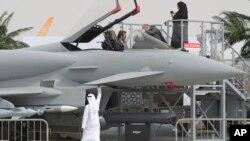 "Seorang pengunjung wanita (atas kanan) dan dua orang lainnya mengamati replika pesawat jet tempur Typhoon di hari pertama Pameran Dirgantara ""Dubai Airshow"" di Dubai (17/11)."