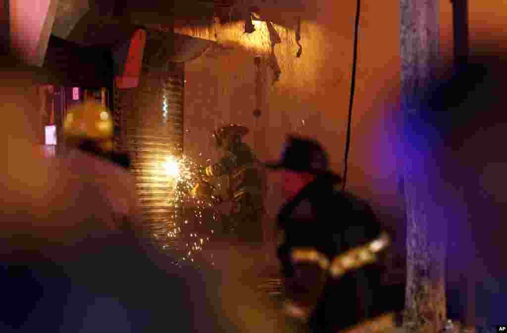 A firefighter saws through a metal wall on a building while battling a fire at the Seaside Park boardwalk on Sept. 12, 2013, in Seaside Park, N.J.