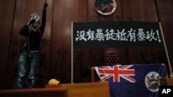 一名進入香港立法會的抗議者站在掛在立法會內的香港殖民地旗幟旁使用擴音喇叭講話。(2019年7月1日)