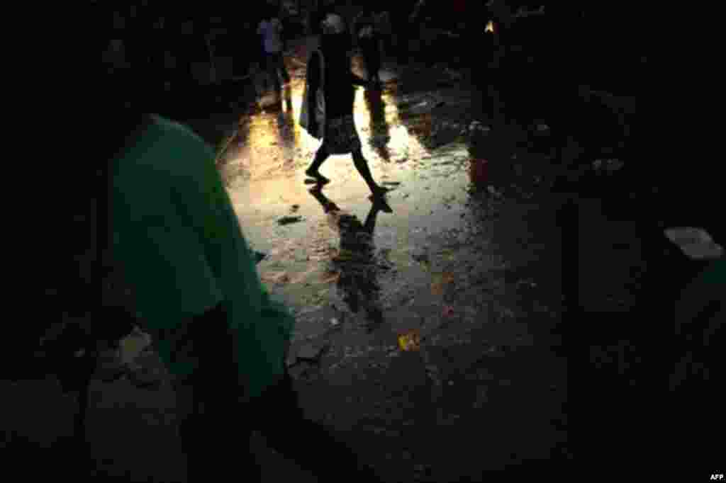 A woman crosses a street covered with dirty water in Port-au-Prince dowtown, Haiti,Thursday, Nov. 11, 2010. (AP Photo/Emilio Morenatti)