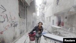 پسری که محمولۀ کوچکی را در منطقۀ تخریب شدۀ شهر حلب سوریه با خود حمل می کند