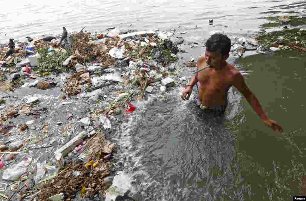 A man brushes his teeth in the polluted water of River Ganga in Kolkata, India.