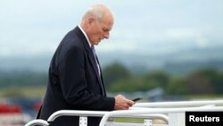 FILE - White House Chief of Staff John Kelly looks down at his phone as he boards Air Force One in Hagerstown, Maryland.