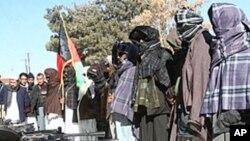 一名前塔利班戰鬥人員(中)一月16日在加茲尼和阿富汗政府的一個儀式上舉著阿富汗國旗